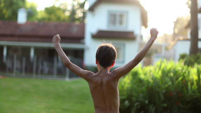 Kid raising arms in the air. Young boy child in victory stand raises fist outside