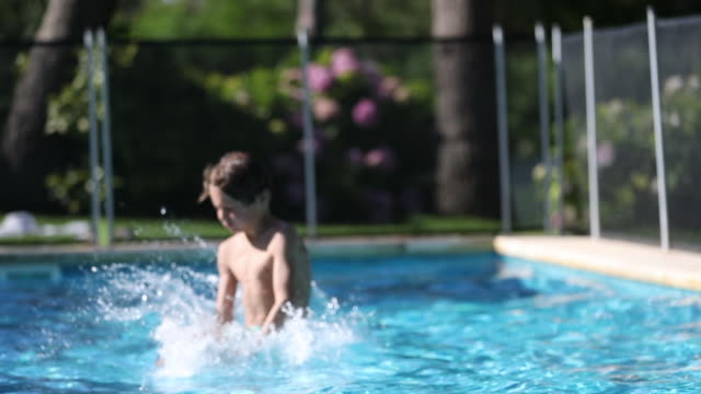 Kid running and jumping inside swimming pool water Kid running and jumping inside swimming pool water one boy only stock videos & royalty-free footage