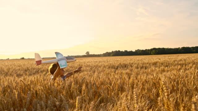 slo mo キッドを走る小麦のフィールドに飛行機トーイ - 男の子点の映像素材/bロール