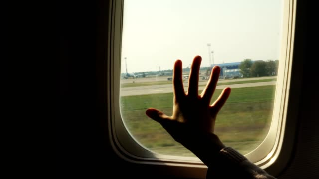 Kid s hand touching airplane window, close up. Silhouette of a child's palm against the background of a window in an airplane. The concept of safety of flights