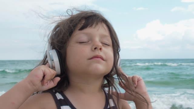 çocuk ritmi başını sallar - kulaklık seti ses ekipmanı stok videoları ve detay görüntü çekimi