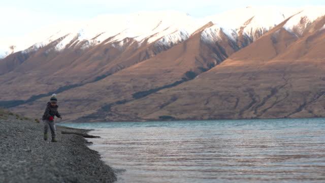 Kid skimming stones in the lake.