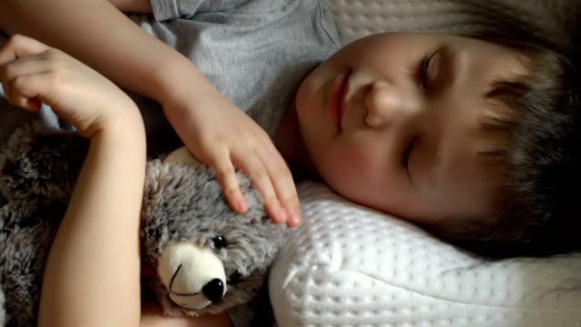 vídeos de stock e filmes b-roll de kid sleeping and caress toy bear - teddy bear