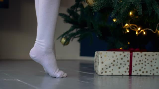 kid står på tiptoes nära julgran - på tå bildbanksvideor och videomaterial från bakom kulisserna