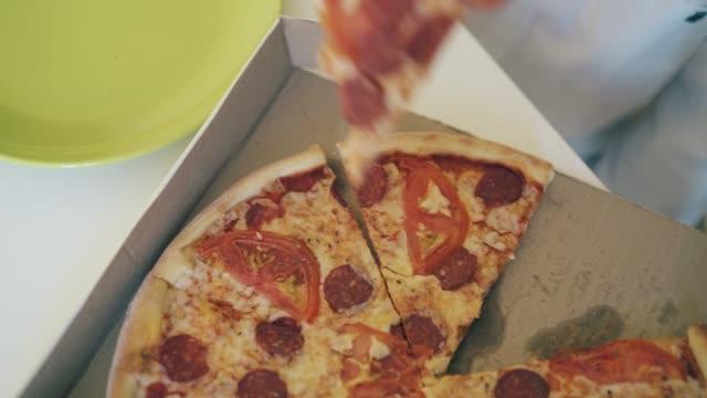 stockvideo's en b-roll-footage met het jong geitje neemt stuk verse pizza en zet op plaat close-up - dikke pizza close up