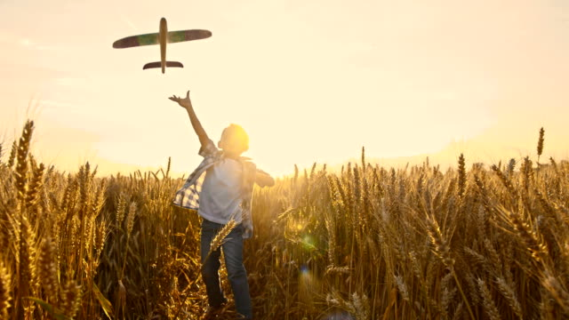 SLO MO Kid throwing airplane toy in wheat field