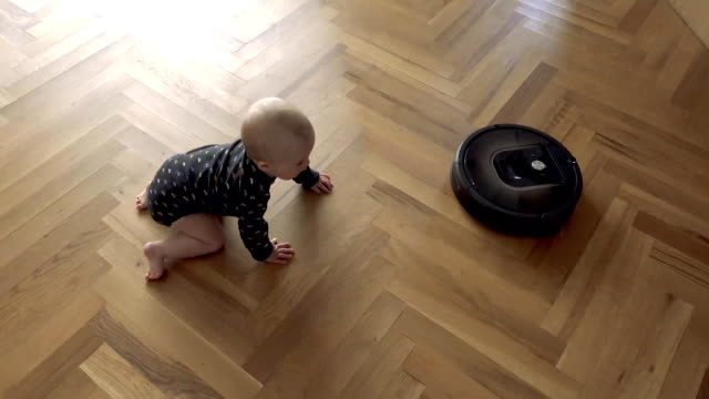 Kid versus Robot Vacuum Cleaner Baby boy versus Robotic vacuum cleaner on wooden fioor view from above chores stock videos & royalty-free footage