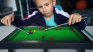 istock Kid wants to make friends. Boy dreams of playing snooker with friends. 1255092100