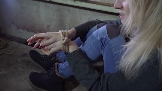 vídeos y material grabado en eventos de stock de una joven rubia secuestrada está sentada en un sótano en un piso de concreto. manos y pies atados con una cuerda. está tratando de liberarse. - human trafficking