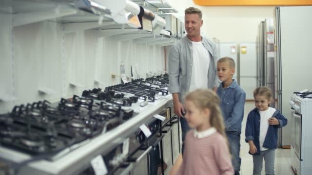 vídeos de stock e filmes b-roll de kids and dad choosing stove in shopping mall - cooker happy