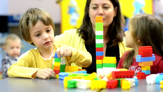 Kids and Educator Playing at Kindergarten Kids and educator playing with plastic building blocks at kindergarten playroom stock videos & royalty-free footage