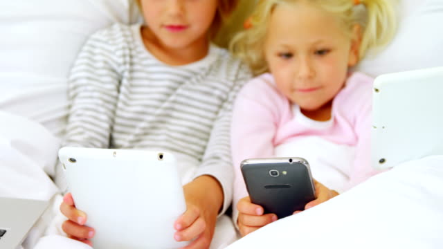 Kids and mother using digital tablet and mobile phone in bedroom 4k video