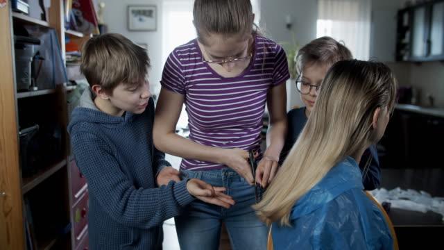 kinder schneiden mutter die haare während der covid-19-pandemie - friseur lockdown stock-videos und b-roll-filmmaterial