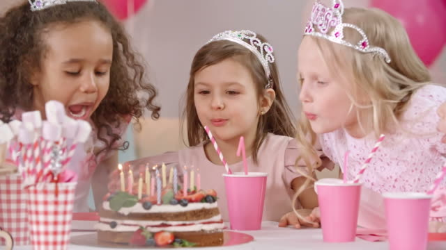 Kids at Birthday Celebration Little girls with tiaras on their heads taking off hands from face and getting surprised about birthday cake on table. They blowing out candles together and clapping hands princess stock videos & royalty-free footage
