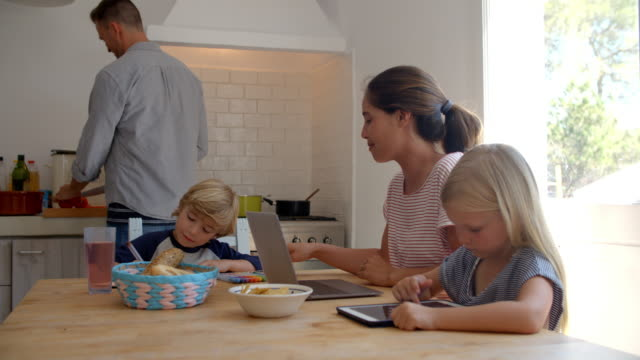 Kids at kitchen table with mum while dad cooks - Vidéo