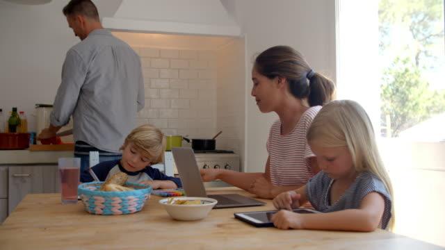 Gosses à la table de cuisine avec la maman tandis que le papa cuisine - Vidéo