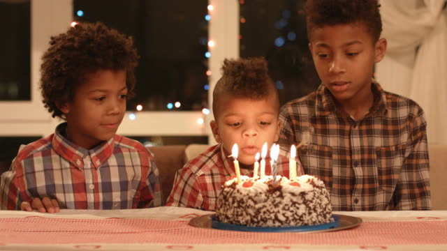 Kids blowing cake's candles out. Kids blowing cake's candles out. Black boys blow candles out. No it's time to eat. Humble birthday party. cousin stock videos & royalty-free footage