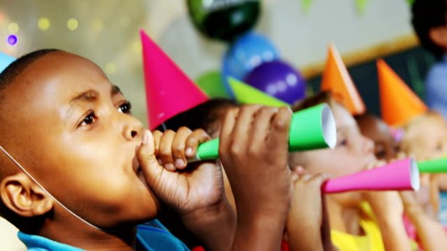 Kids blowing party horns during birthday party 4k video
