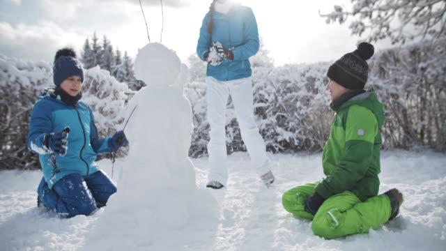 vídeos y material grabado en eventos de stock de niños construyendo un hombre de nieve en un día de invierno - snowman