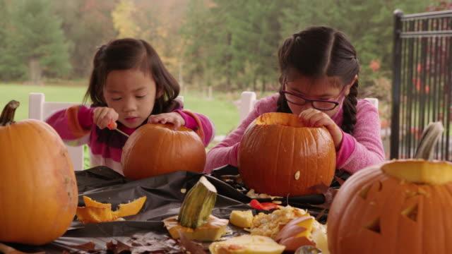 kids carving pumpkins for halloween - pumpkin стоковые видео и кадры b-roll