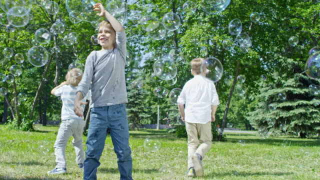 Kids Chasing Bubbles on Green Lawn in Park video