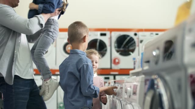 Kids Choosing Washing Machine with Father in Home Appliance Store Happy father enjoying shopping with kids in home appliance store: little girls and their brother smiling and playing with washing machine appliance stock videos & royalty-free footage
