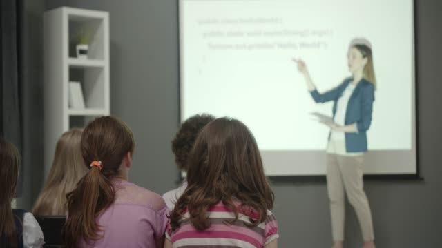 Kids Coding Kids learning to code in their school. Young female teacher having presentation. She is standing in front of projection screen and talking to kids. They are sitting and listening carefully. elementary age stock videos & royalty-free footage
