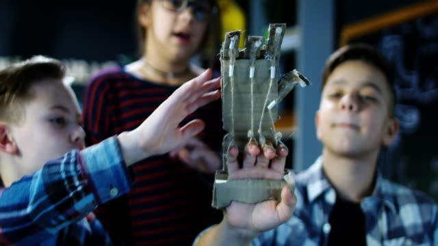 Crianças desenvolvendo braço de papelão - vídeo