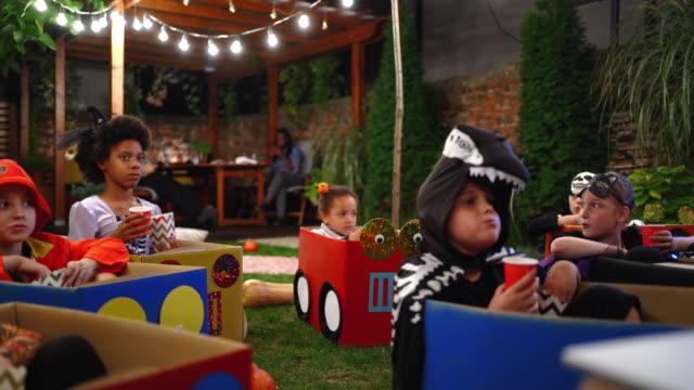 vídeos y material grabado en eventos de stock de niños vestidos para halloween viendo película en el cine en casa patio trasero - halloween covid
