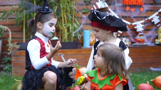 Kids eating candy at Halloween party in their backyard Kids eating candy at Halloween party in their backyard halloween covid stock videos & royalty-free footage