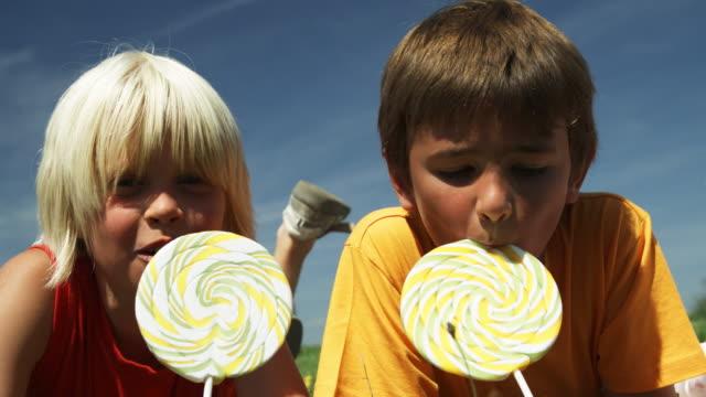 kids eating lollies (shot on red) - 波板糖 個影片檔及 b 捲影像