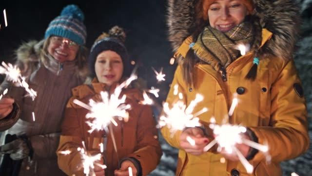 kids enjoying sparklers at new year's eve night - предподростковый возраст стоковые видео и кадры b-roll
