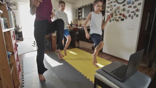 bambini che si esercitano a casa durante la pandemia di covid-19 - esercizio fisico video stock e b–roll