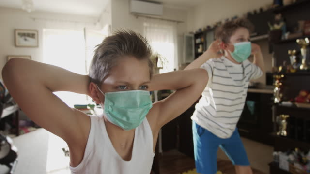 Kids exercising at home during the COVID-19 pandemic During the COVID-19 pandemic kids are training at home using online tutorials. Kids are doing squat exercises. BMPCC 4K , RAW Q0 stay home stock videos & royalty-free footage