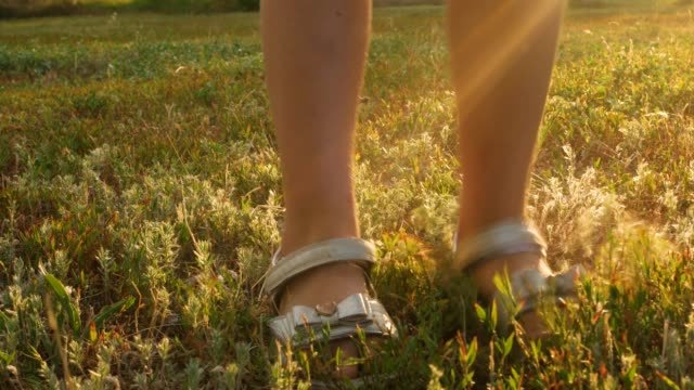 Kids feet legs jumping on colorful red green autumn grass. Calves of a child in sandals walking on forest path. Child's shoes running on pathway close up. Joyful people, active lifestyle on fresh air.