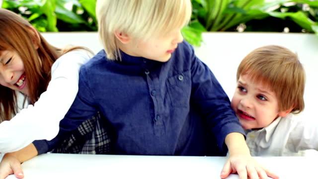 vídeos de stock e filmes b-roll de crianças brigando na tabela - brigar