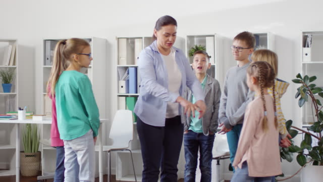 Kids Forming Circle around School Counselor Knee-up shot of 30-something female school counselor leading group support session for six young teenagers, dressed in casual clothes, and instructing them to stand in circle around her school counselor stock videos & royalty-free footage