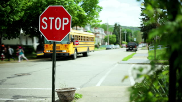 Kids get of school bus next to stop sign Kids get of school bus next to stop sign goodbye single word stock videos & royalty-free footage