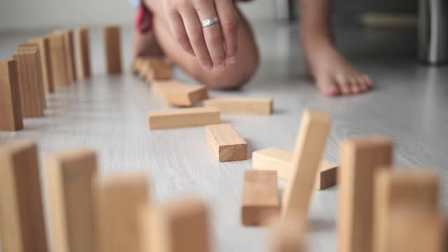 Kid's hand playing Dominos on the floor at home, slow motion.