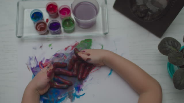 Kids hands drawing by multi-colored paints on white paper sheet. Top view of child finger painting.