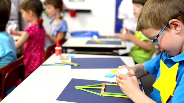 stockvideo's en b-roll-footage met kinderen hebben van craft project op kleuterschool - schooljongen