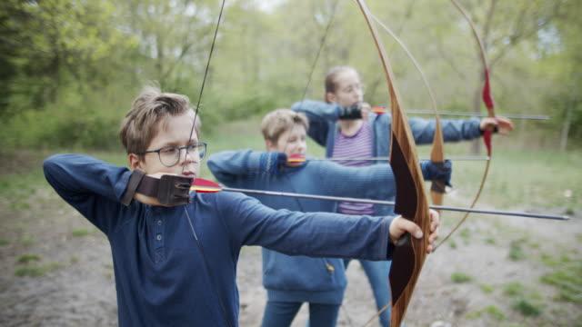 vidéos et rushes de gosses ayant l'amusement tirant des arcs dans la forêt - tir à l'arc
