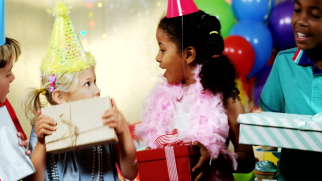 Kids holding gift boxes during birthday party 4k video
