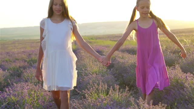 kids in lavender flowers field at sunset in the dresses - wschodnio europejski filmów i materiałów b-roll