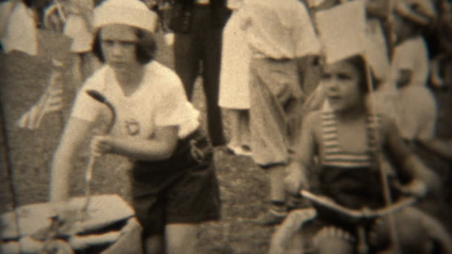 1938: Kids in naval sailor hats riding bikes in patriotic American parade.