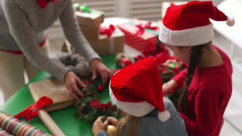 Kids in Santa Hats and Woman Decorating Christmas Wreath High angle of two little girls in Santa hats and woman making decorative Christmas wreath in craft studio craft stock videos & royalty-free footage