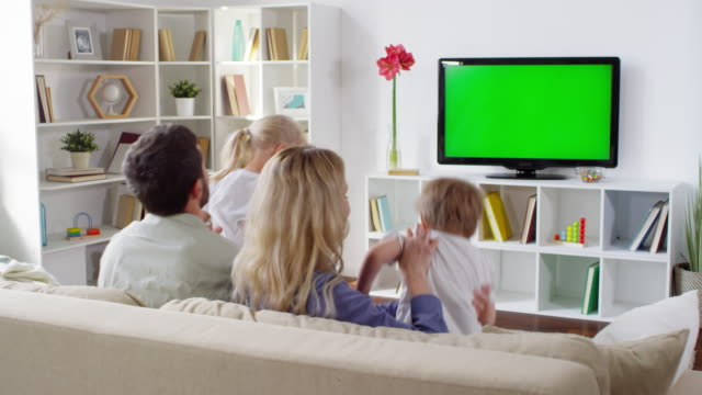 Kids Joining Parents Watching TV in Living Room Medium shot of excited little children running to parents sitting on sofa and watching TV in living room family watching tv stock videos & royalty-free footage
