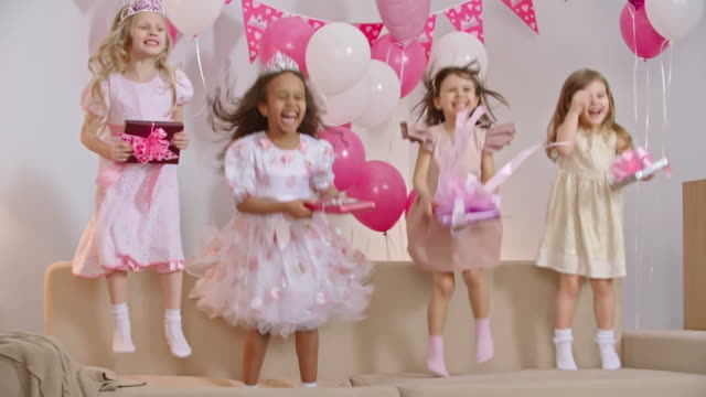 Kids Jumping With Birthday Presents Four little girls dressed like princesses jumping on sofa decorated with balloons and holding gift boxes in slow motion princess stock videos & royalty-free footage