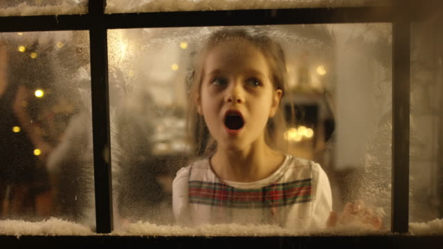 Kids looking out of the snowy window video