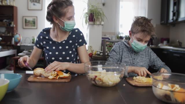 vídeos de stock, filmes e b-roll de crianças fazendo salada de frutas em casa durante pandemia covid-19 - fruit salad